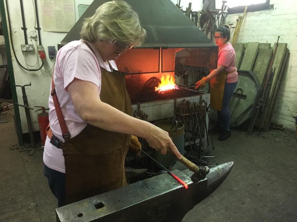 People at the forge.  Once hammering on an anvil and one in the fire on a team day experience