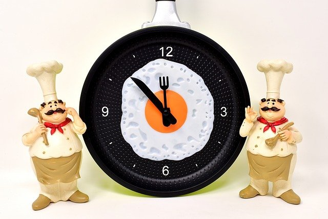 Two cartoon chefs beside a clock with an fried egg in the centre