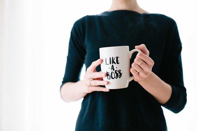 Lady holding a large white mug that says 'Like a Boss'