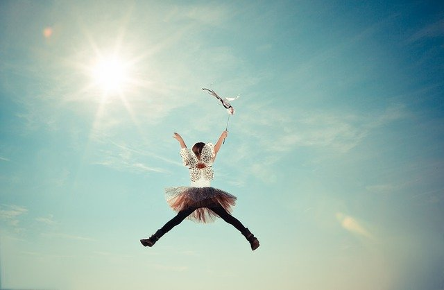 Woman in tutu jumping into the sky with a wand in her hand