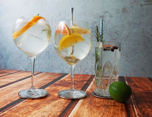 Two balloon glases and one tall glass each with gin and tonic, ice, lemon and lime