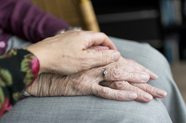 A younger person's hand over an older person's hand in care/support