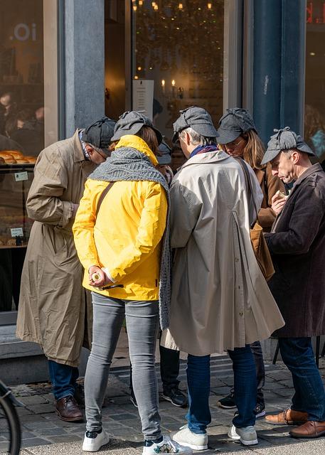 A group of people in a huddle on the street each wearing a deerstalker hat
