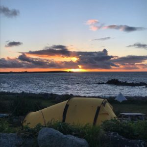 Sunset over sea, with tent in the foreground