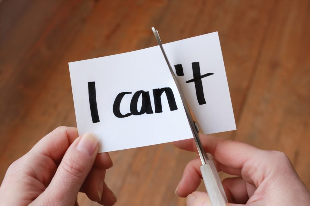 Someone cutting a piece of paper with I can't written on it, to make I can