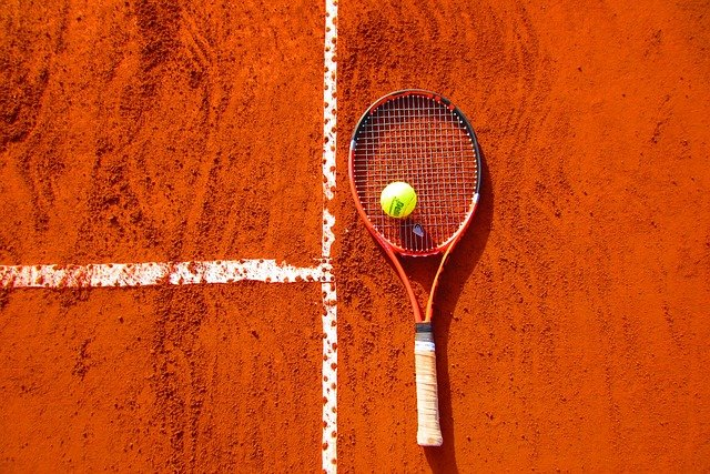 Tennis racket and ball on the floor by the lines of a clay court