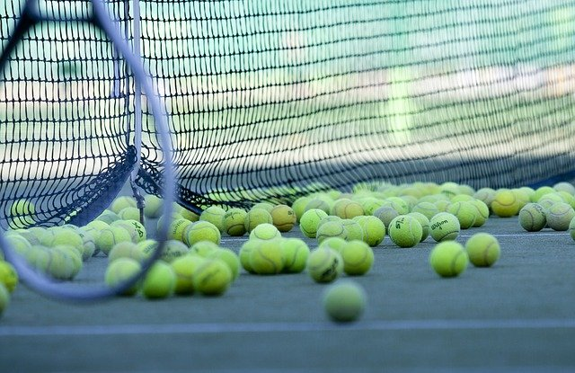 Tennis balls all gathering at the base of a tennis net with racket leaning on net